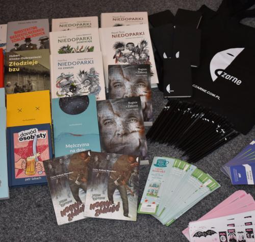 Na zdjęciu znajdują się materiały otrzymane od różnych wydawnictw. Są wśród nich książki, audiobooki, zakładki, torby, notesy i ołówki.