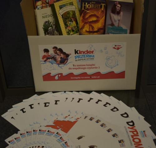 Na zdjęciu widoczne są książki podarowane przez czytelników w ramach akcji organizowanej przez firmę Ferrero, a także dyplomy, zakładki do książek i karty do gry dla dzieci biorących udział w przedsięwzięciu.