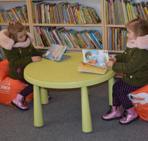 Zdjęcie przedstawia dwie dziewczynki w wieku przedszkolnym czytające bajki na pufach z logiem firmy Kinder w bibliotece.