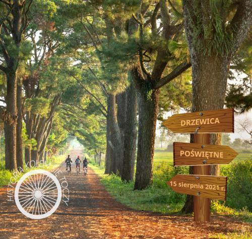 Trzech rowerzystów przemierza leśną  aleję. Drogowskaz umieszczony na drzewie informuje o kierunkach  Drzewicy i Poświętnego oraz o dacie rajdu.